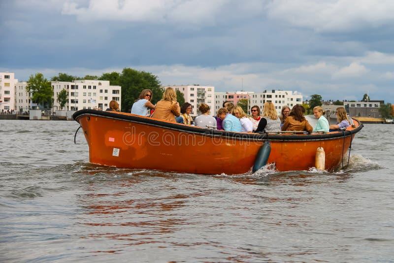 Люди в шлюпке на путешествиях каналов Амстердама стоковая фотография rf