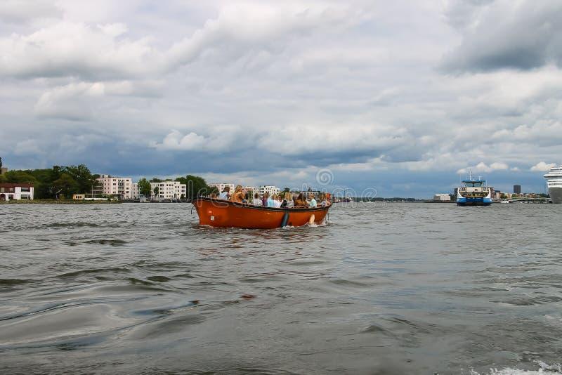 Люди в шлюпке на путешествиях каналов Амстердама стоковое изображение