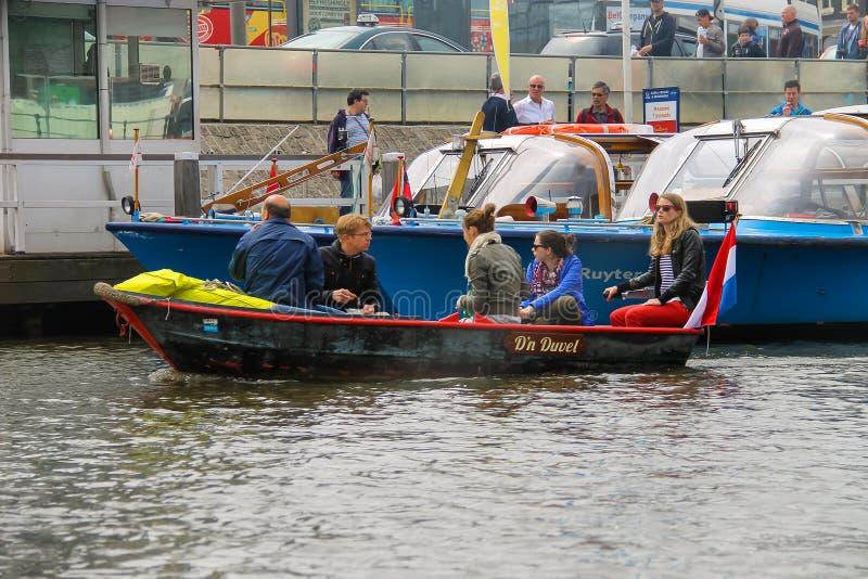 Люди в шлюпке на путешествиях каналов Амстердама стоковая фотография