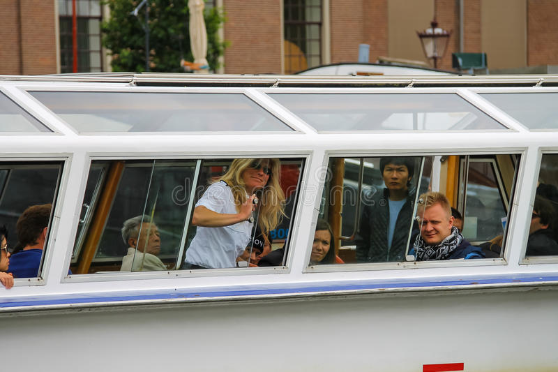 Люди в шлюпке на путешествиях каналов Амстердама стоковые изображения rf