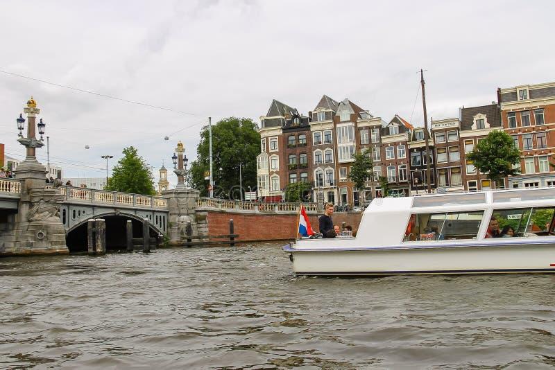 Люди в шлюпке на путешествиях каналов Амстердама стоковое фото rf