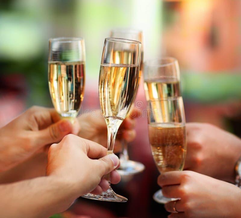 Люди держа стекла шампанского делая здравицу стоковое фото rf