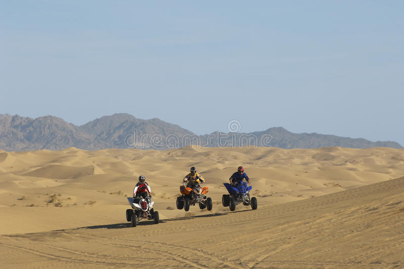 Люди ехать велосипеды квада в пустыне стоковая фотография rf
