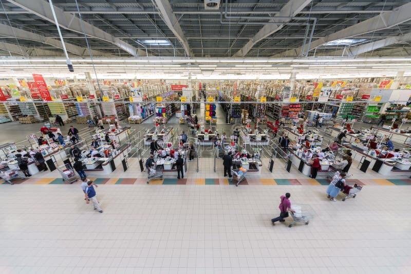 Люди делают приобретения в superstore Auchan стоковые фотографии rf