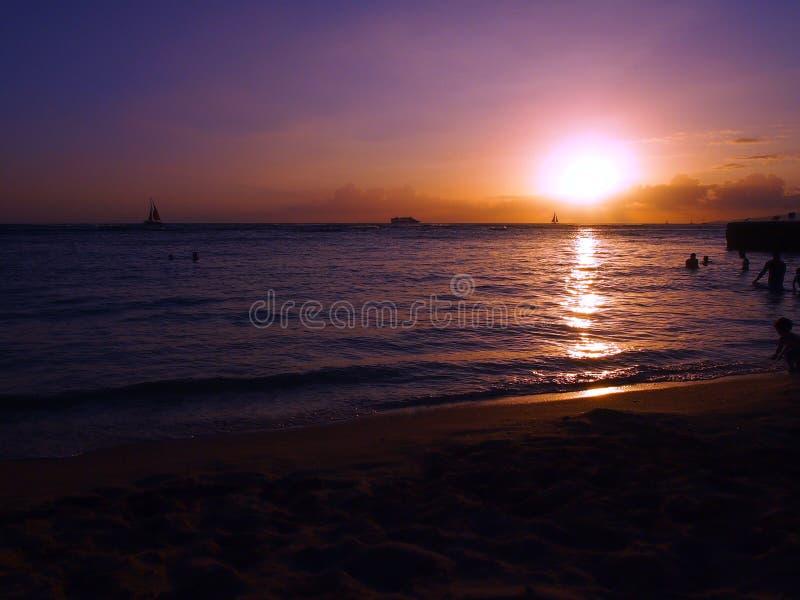 Люди играют в воде с драматическим заходом солнца на пляже Kaimana стоковое изображение rf