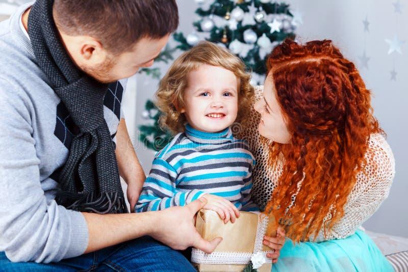 Люди и ель семьи из трех человек рождества счастливые с подарочными коробками над белой предпосылкой спальни стоковое изображение rf