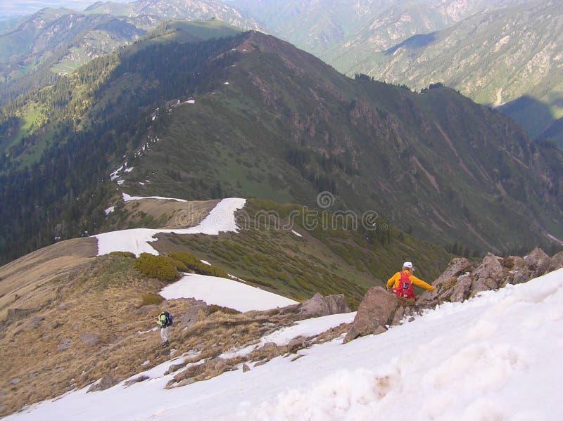 Люди идут вниз от вершины горы на снежном гребне стоковые фото