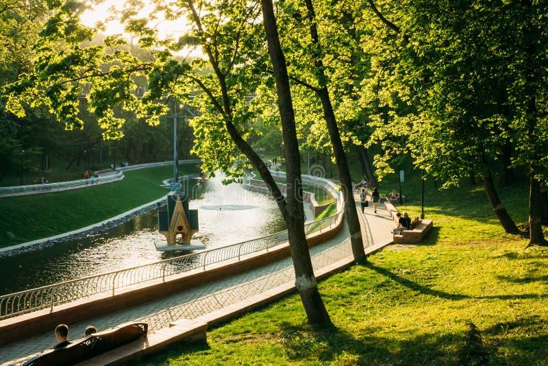 Люди идут вокруг парка города во время захода солнца внутри стоковая фотография