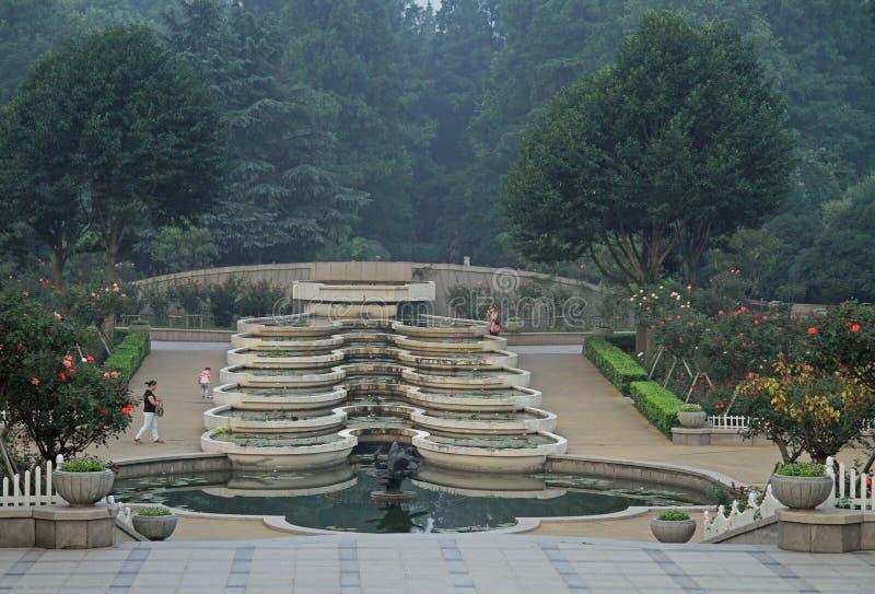 Люди идут на многоуровневый фонтан в парке стоковые фото