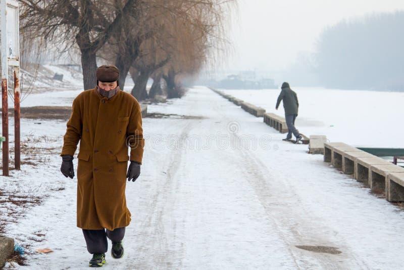 Люди идя на замороженный Tamis реки в Pancevo, Сербии должной к исключительно холоду над Балканами стоковые фотографии rf