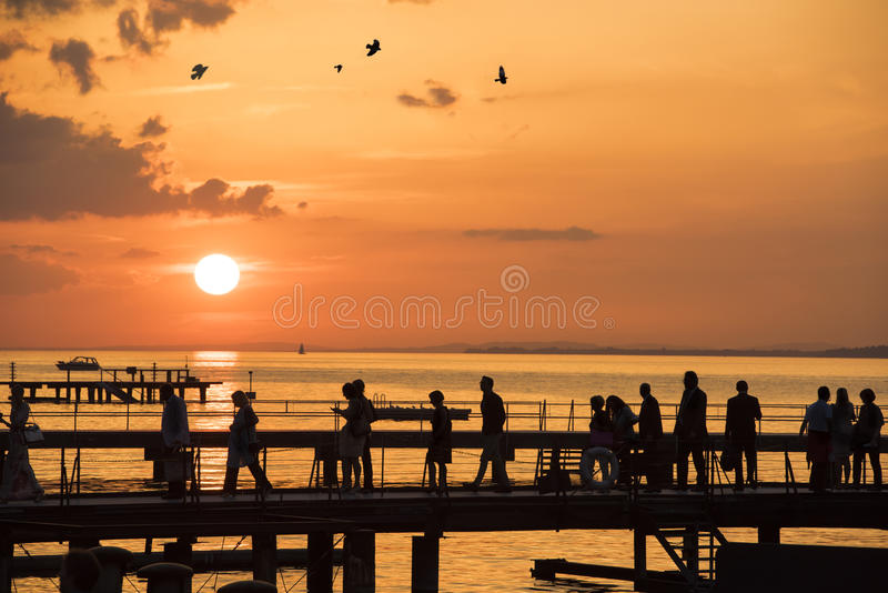 Люди идя на заход солнца над мостом на озере