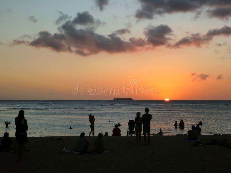 Люди наблюдают драматический заход солнца на пляже Сан Souci стоковое изображение