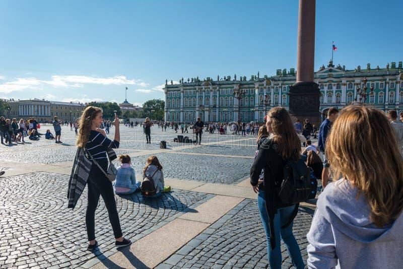Люди наслаждаются искусством музыканта в квадрате дворца, St улицы стоковая фотография rf