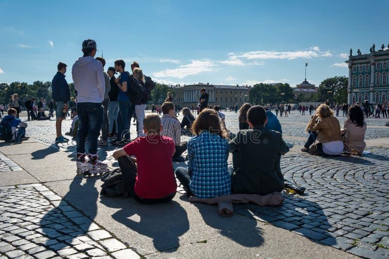Люди наслаждаются искусством музыканта в квадрате дворца, St улицы стоковые фото