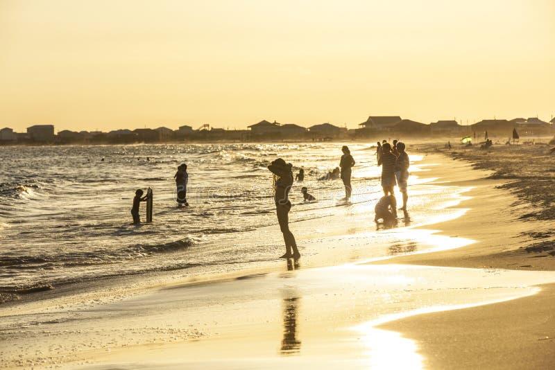 Люди наслаждаются красивым пляжем в позднем вечере на дофине i стоковые фотографии rf