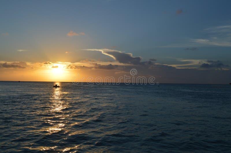 Люди наслаждаясь карибским заходом солнца на маленькой шлюпке, разделением, чеканщиком Caye, Белизом стоковое изображение rf