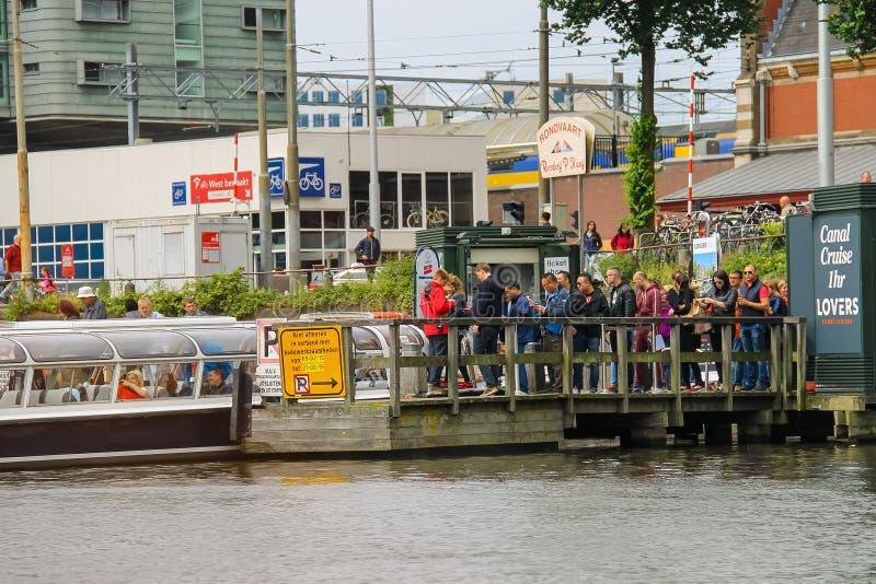 Люди на посадке на туристических суднах реки, Амстердаме дока, сети стоковое фото rf