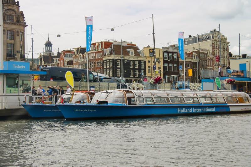Люди на посадке на туристических суднах реки, Амстердаме дока, сети стоковая фотография rf