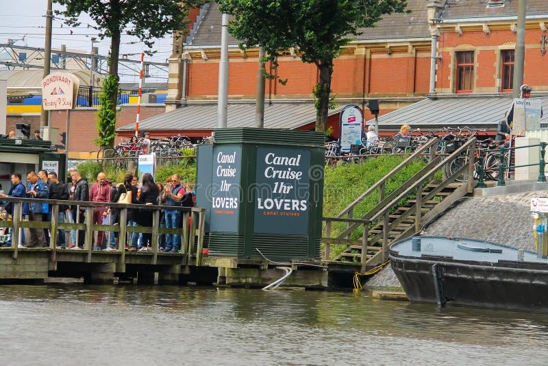Люди на посадке на туристических суднах реки, Амстердаме дока, сети стоковые фотографии rf