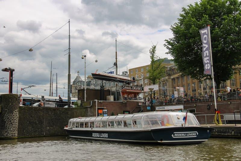 Люди на посадке на туристических суднах реки, Амстердаме дока, сети стоковые изображения