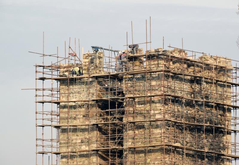Люди на работе, работники отремонтировали старую крепость стоковые изображения
