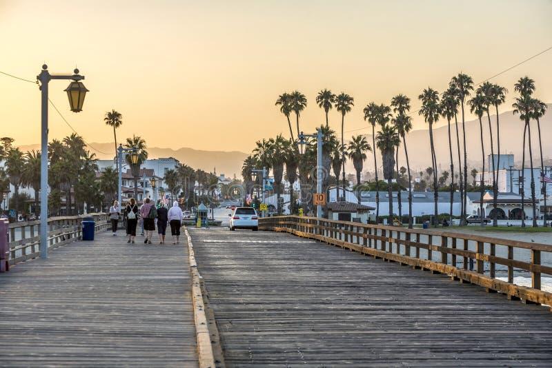 Люди на сценарной старой деревянной пристани в Санта-Барбара в заходе солнца стоковое изображение rf