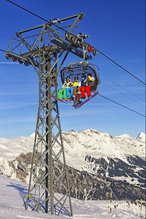 Люди на лыже и сноуборды на кабине фуникулера на спорте зимы стоковые изображения