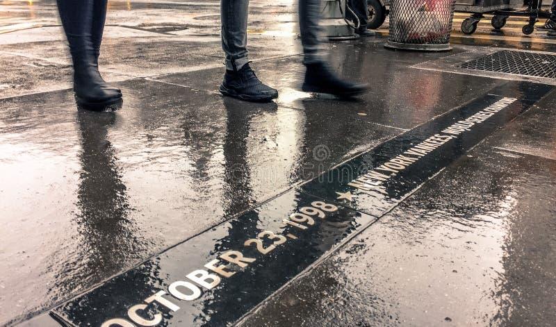 Люди Нью-Йорка идя через дождь стоковое фото