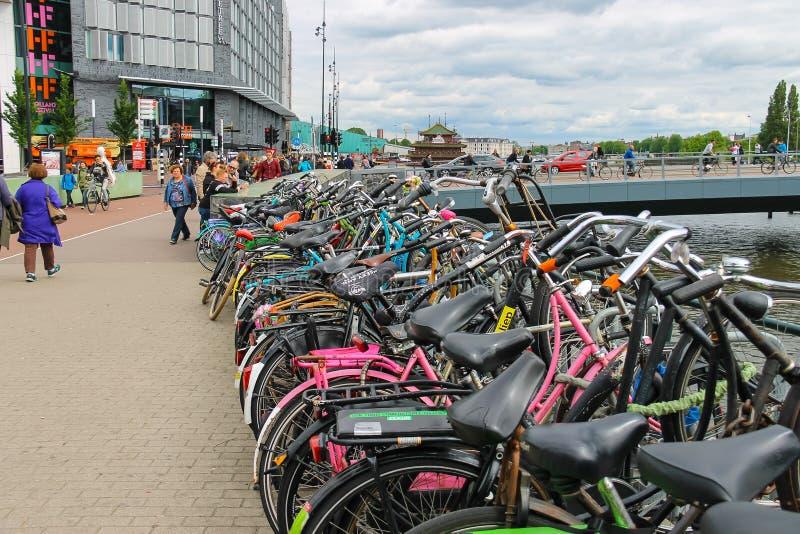 Люди около автостоянки велосипеда около канала в Амстердаме стоковая фотография rf