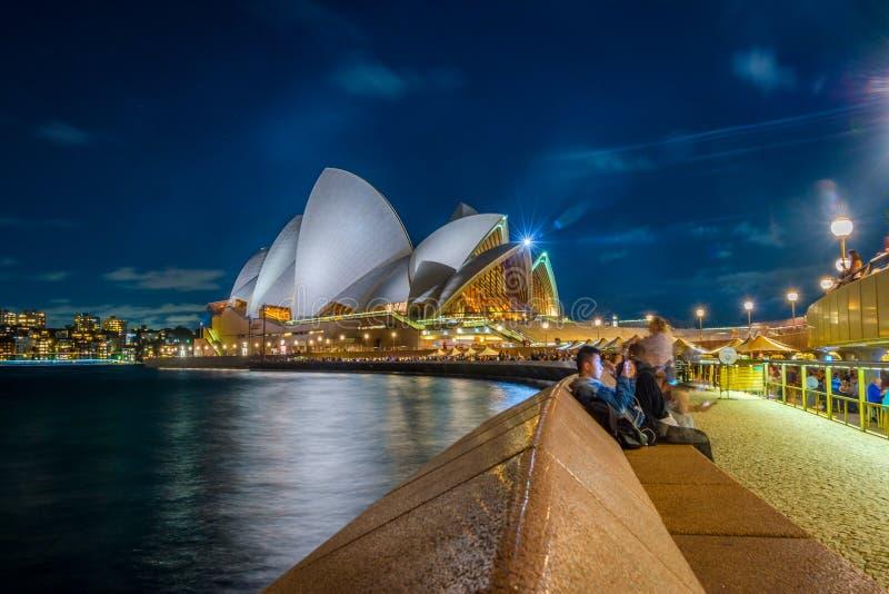 Люди оперным театром Сиднея на ноче стоковые изображения