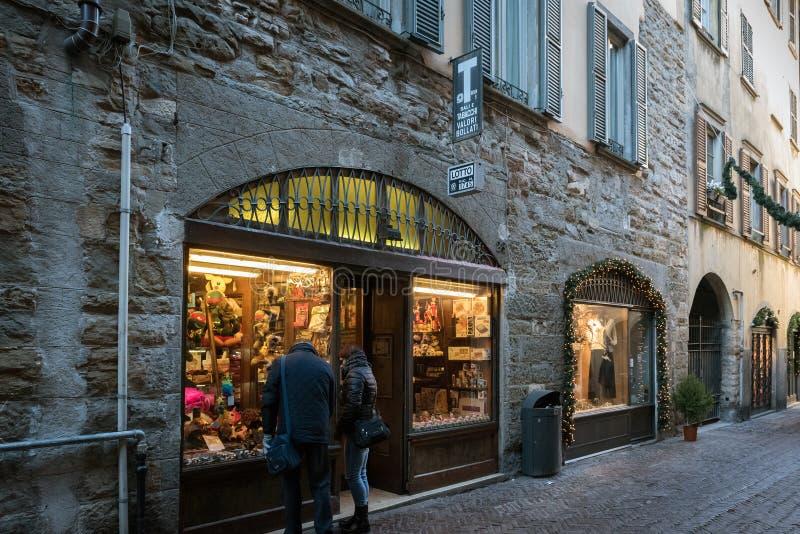 Люди остаются близко сувенирным магазином на центральной улице городка Бергама старого стоковое фото