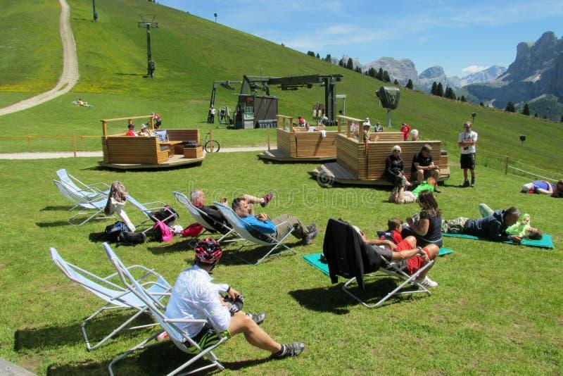 Люди ослабляя в горах приближают к refugio, ресторану в Альпах стоковое изображение