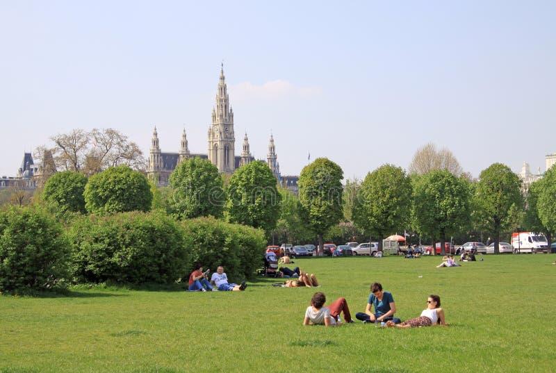 Люди ослабляя в парке в вене около дворца Hofburg имперского с здание муниципалитетом вены на заднем плане стоковые фото