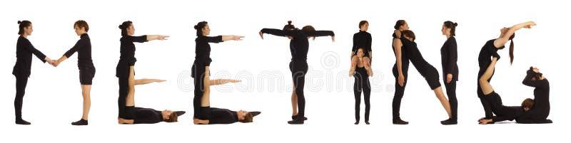 Люди одетые чернотой формируя слово ВСТРЕЧИ стоковые фотографии rf