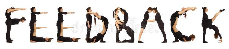 Люди одетые чернотой формируя слово ОБРАТНУЮ СВЯЗЬ стоковое фото