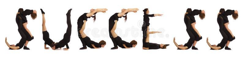 Люди одетые чернотой формируя слово УСПЕХ стоковая фотография