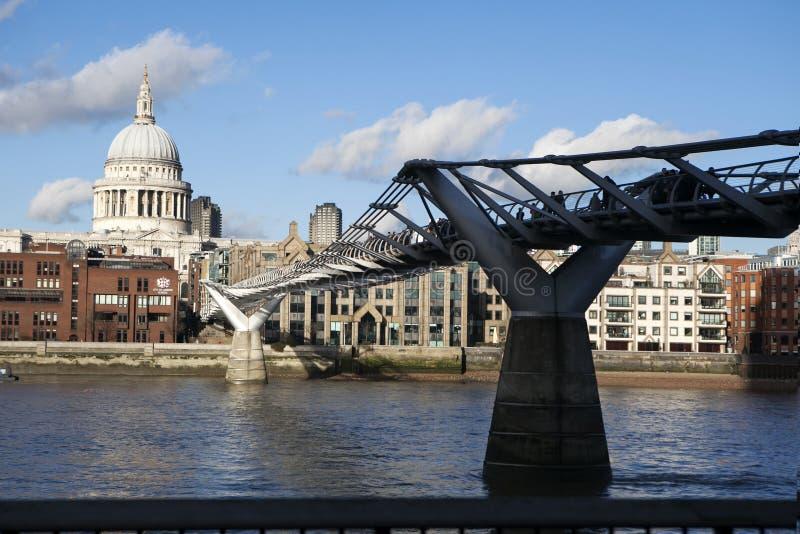 Люди пересекая мост тысячелетия над рекой Темзой соединяя город Лондона с южным берегом стоковые изображения
