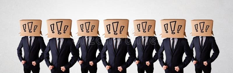 Люди показывать с восклицательными знаками на коробке на их голове стоковая фотография rf