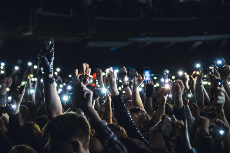 Люди принимая фотоснимки с умным телефоном во время концерта музыки Персона захватывая видео на мобильном телефоне на музыкальном стоковое изображение rf