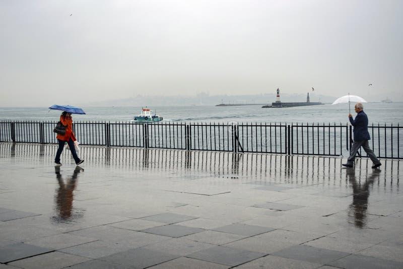 Люди пристани парохода Стамбула идя в дождь стоковые изображения