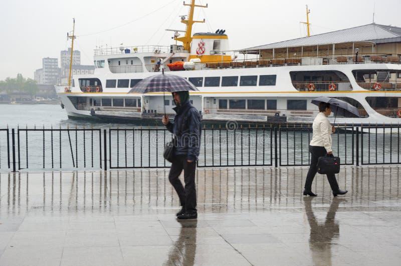 Люди пристани парохода Стамбула идя в дождь стоковые фото