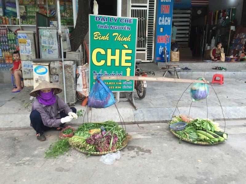 Люди продавая овощи на улице в Thai Nguyen, Вьетнаме стоковое изображение