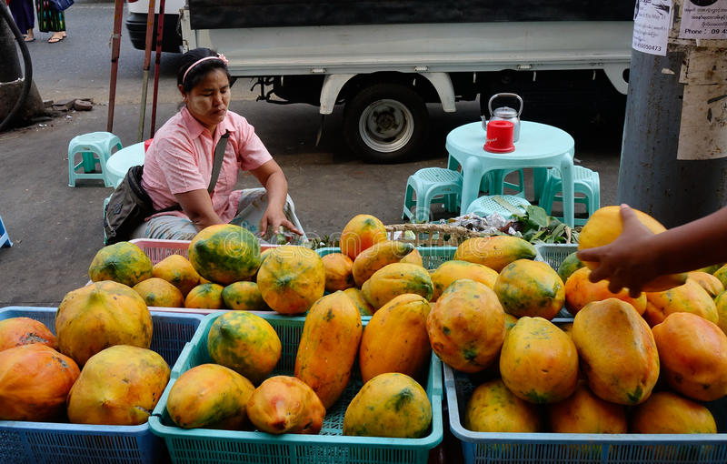 Люди продавая папапайю приносить на рынке в Янгоне, Мьянме стоковые фотографии rf