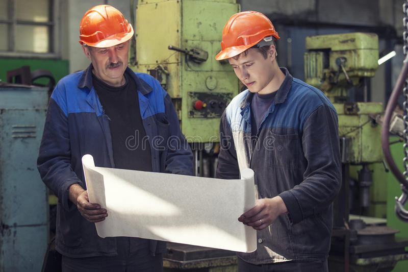 Люди работают на старой фабрике для установки оборудования стоковое фото rf