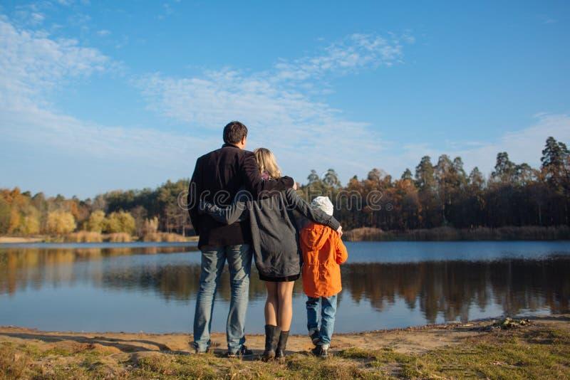 Люди семьи из трех человек на стороне озера стоковые изображения rf