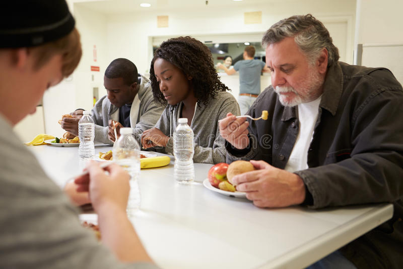 Люди сидя на таблице есть еду в приюте для бездомных стоковые фотографии rf