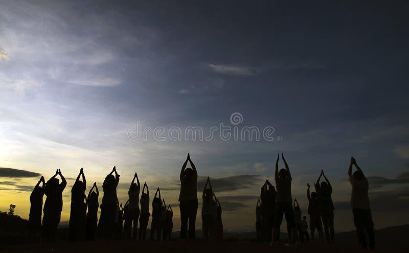 Люди с йогой на горе стоковые фотографии rf