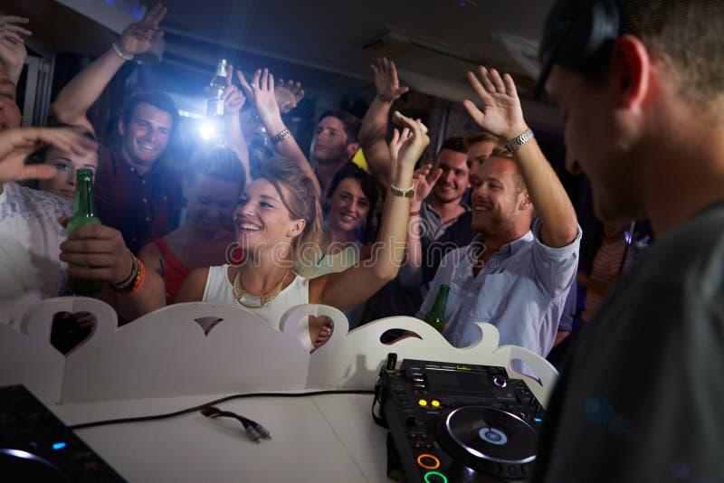 Люди танцуя в ночном клубе с DJ в переднем плане стоковая фотография