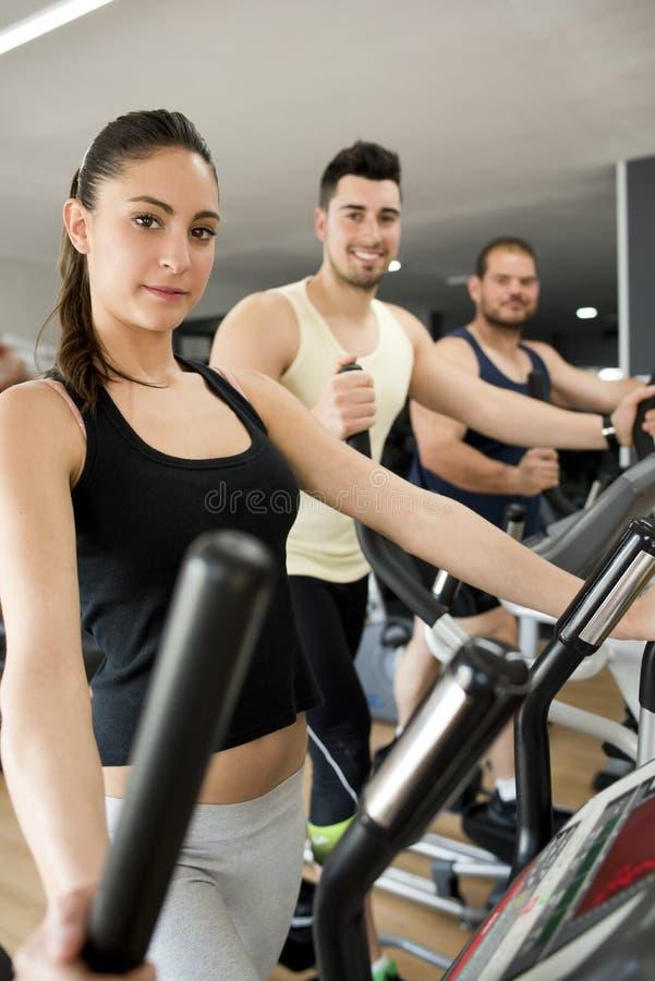 Люди тренируя на велосипеде перекрестного тренера эллиптическом стоковые фотографии rf