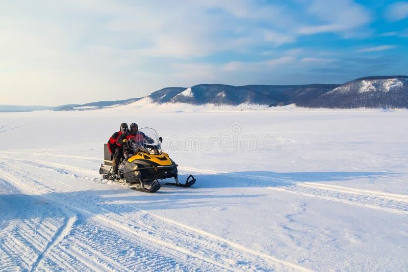 Люди управляя снегоходом в горе зимы стоковые изображения rf